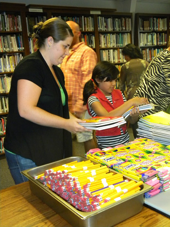 Peyton Erb (left) works in the assembly line putting MCC school kits together. Photos courtesy of authors