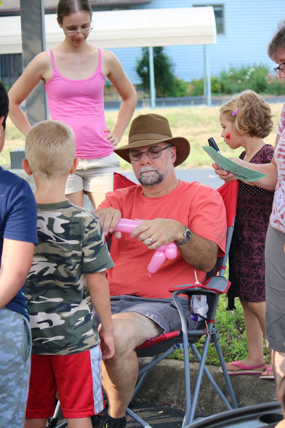 Phil Kniss, pastor of Park View Mennonite Church, creates a balloon animal at a neighborhood Kids Club Block Party. Photo by Trina Trotter Nussbaum