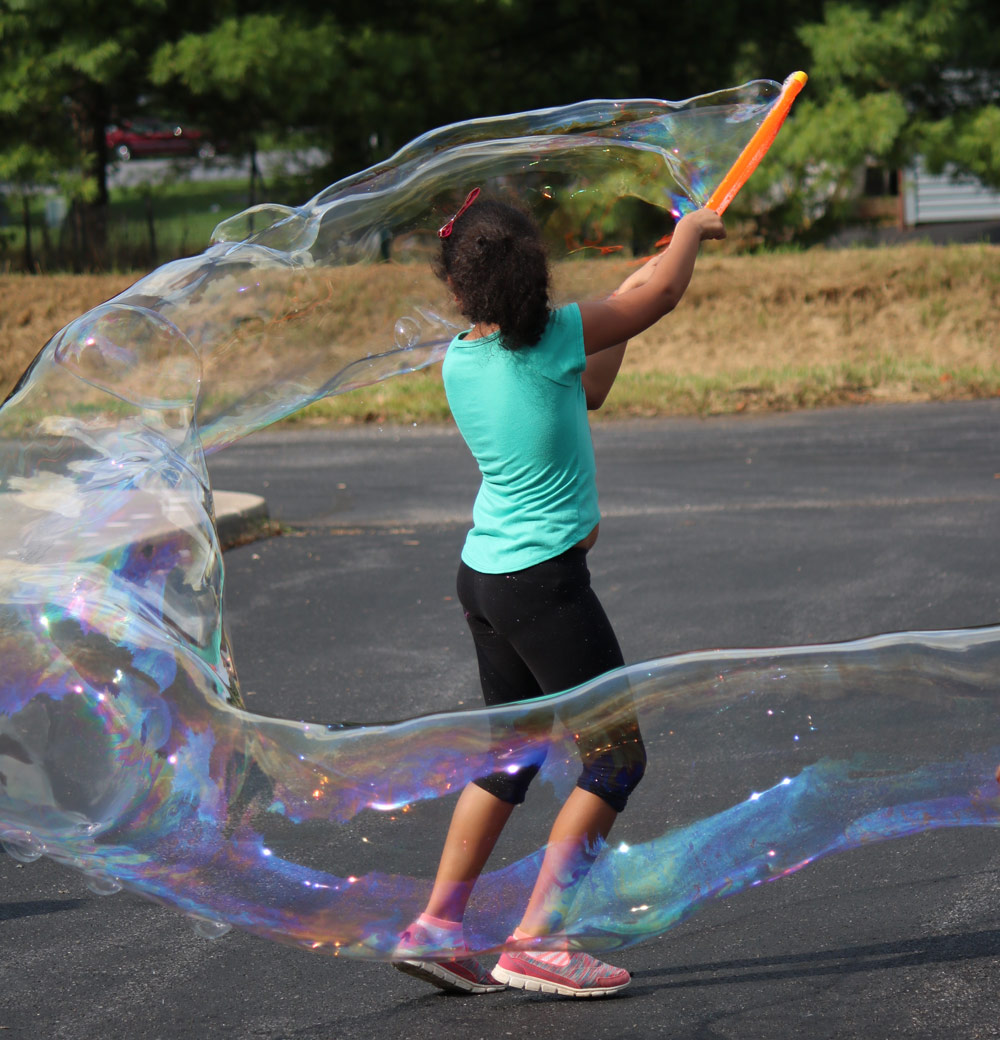 A young participant at the Kids Club Block Party enjoys creating huge swirls of bubbles. Photo by Trina Trotter Nussbaum