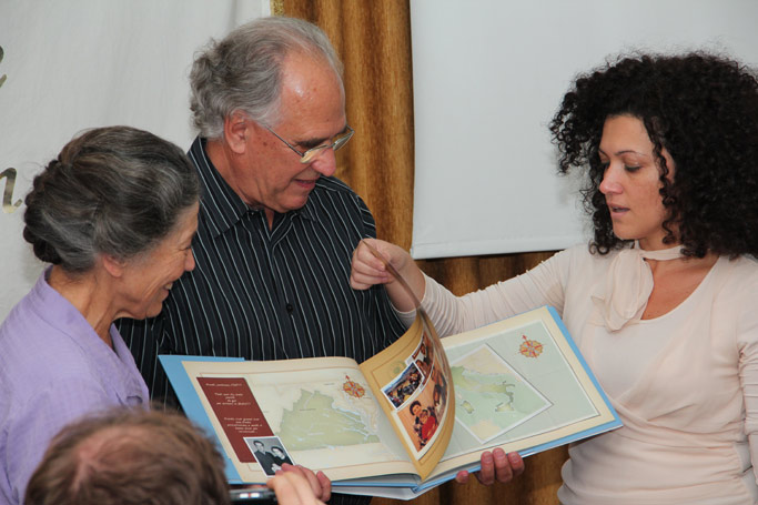 Mara Colonna (right) presents Eva and Willard with a photo book celebrating the many years and lives touched at Centro Koinonia.