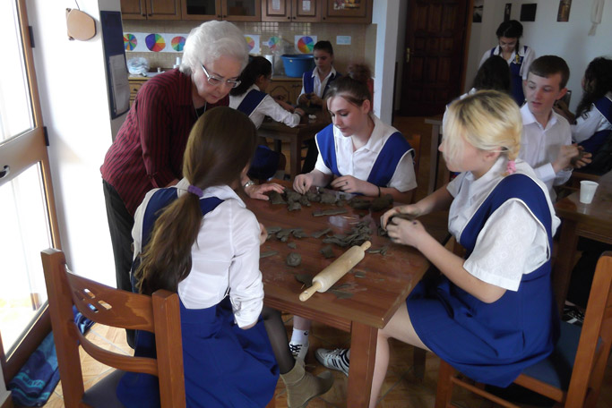 Esther Augsburger helps students work with clay in a pottery class.