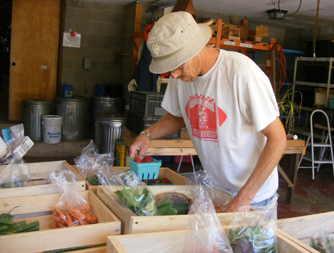 Joel Dollarhite, a tranSender working at OCF, assembles the  contents of a CSA (community supported agriculture) basket.