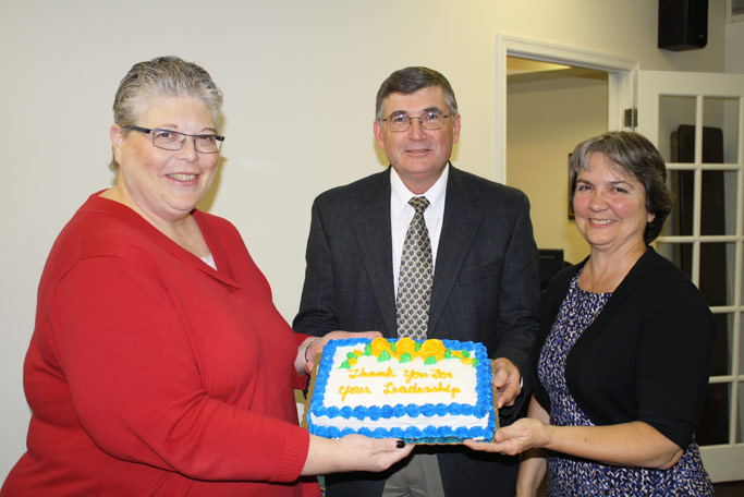 Board chair Phyllis Miller (left) presents a cake to Loren and Earlene Horst, thanking them for their long service to Virginia Mennonite Missions.