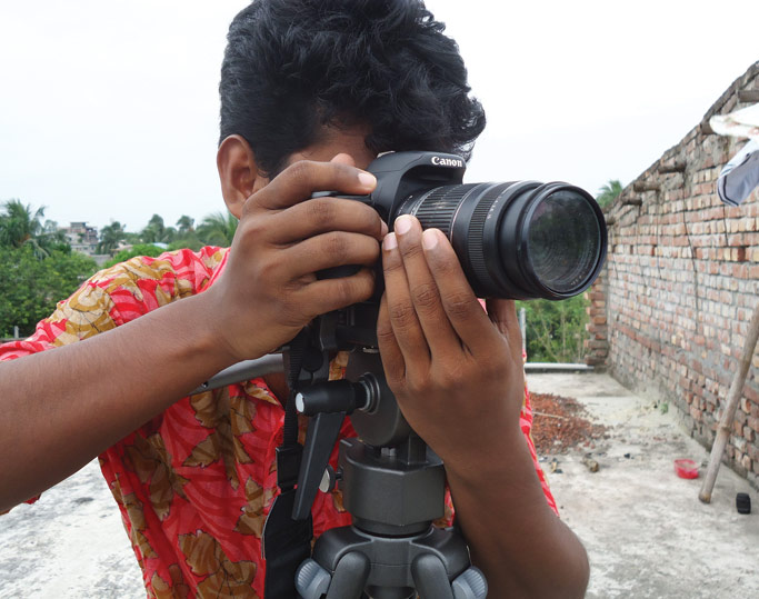 A young man in the community takes images for a new multimedia business. Courtesy photo.