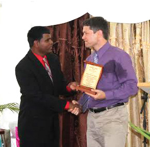 Deolal Ramdial, MCTT president, presents a token to Aaron Kauffman, president of VMMissions, during the 40th anniversary celebrations. Courtesy photo