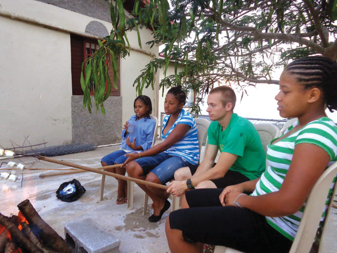 Caleb roasts marshmellows over a fire with youth from the Ridge church in Jamaica, after a Bible study.  Courtesy photo
