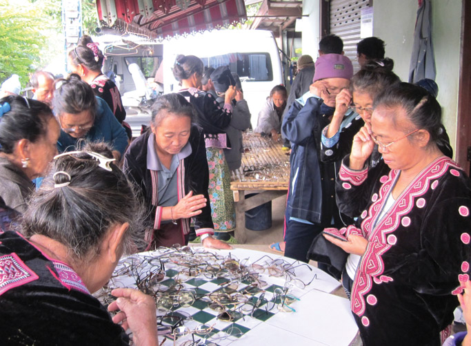 Hmong villagers sort through piles of donated glasses from a North  Carolina chapter of the Lion's Club. Photo: Jonah Yang