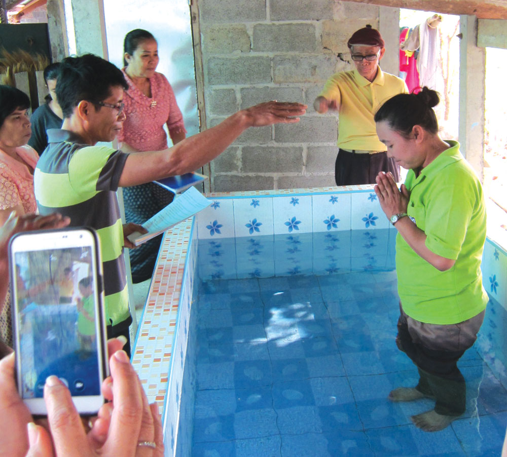 Mother Mon is baptized by Pastor Joi (at left) in late March, less than two months after her daughter Ying's funeral.