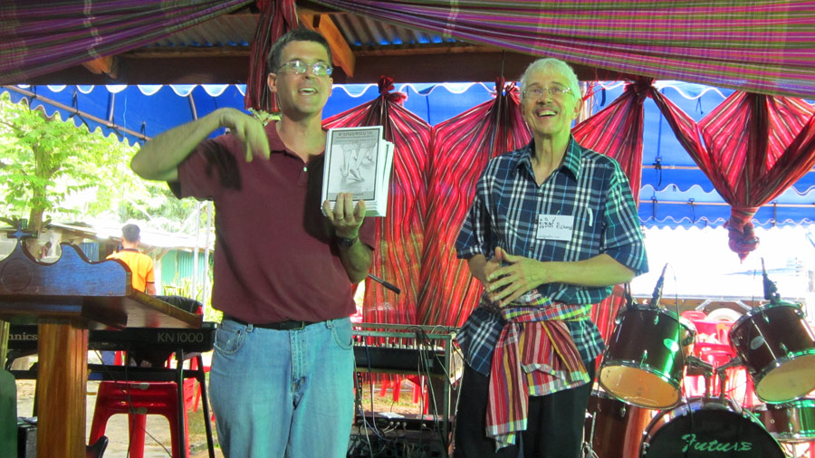"""Mark Schoenhals and Richard Showalter introduce Richard Showalter's book, """"Footprints of God,"""" translated into Thai for the event. Photo by Carol Tobin"""
