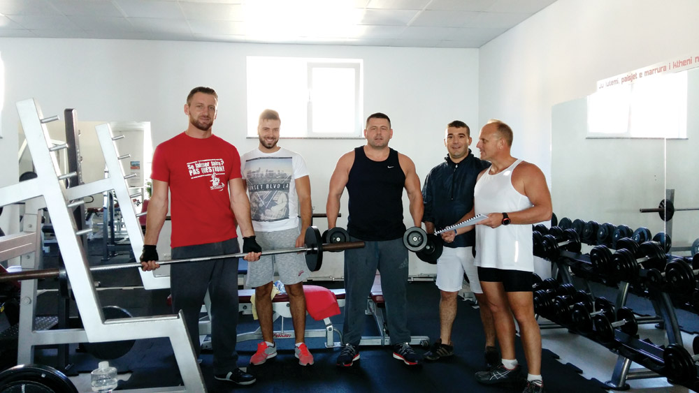 (From left) Granit, Bledor, Bek, Valdet and author Vince at the fitness center. Vince is holding his training schedule.  Photo courtesy of author