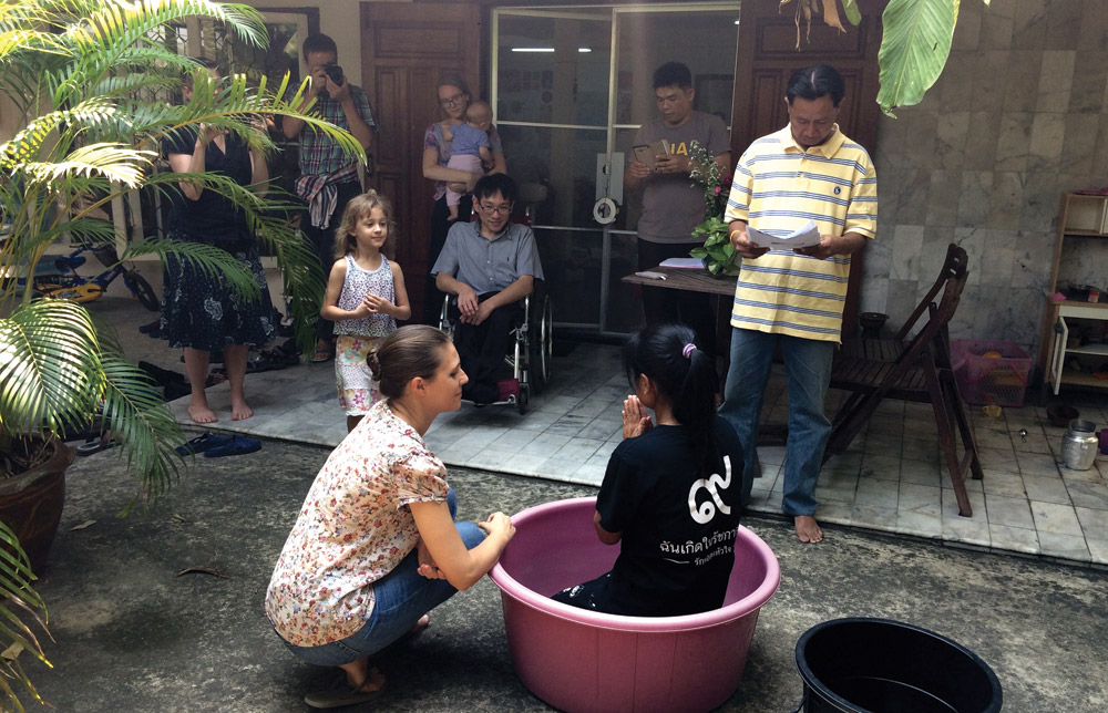 The baptism of P Jan, with P Jaa officiating, and local partners Khun Koch (seated) and P Ehk (standing) joining in the celebration. Also pictured is the author (kneeling), her husband Steve Horst and their two children, and Jessamyn Tobin. Photo by Lynn Suter