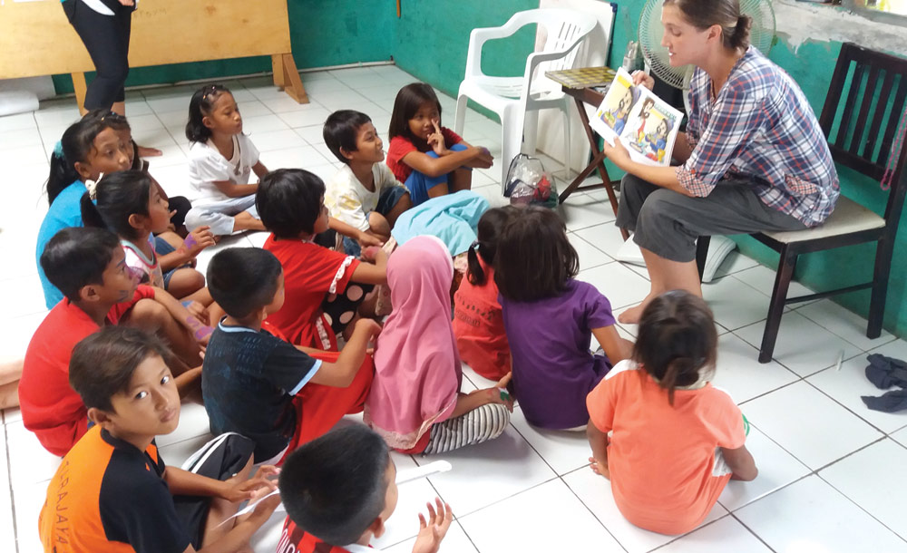 Grace reads a Bible story book to children at Rumah Harapan (House of Hope) where she serves in Southeast Asia.