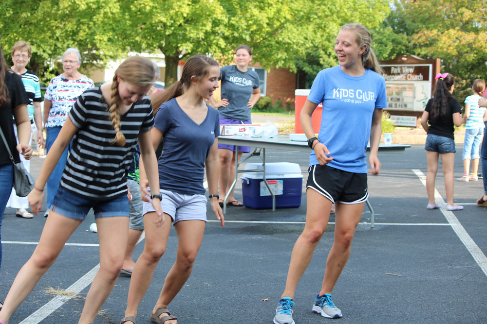 At Park View Mennonite Church's Kids Club Block Party, Michaela Mast teaches Sarah Keim (left) and Hannah Mast steps to a song. Photo by Trina Trotter Nussbaum