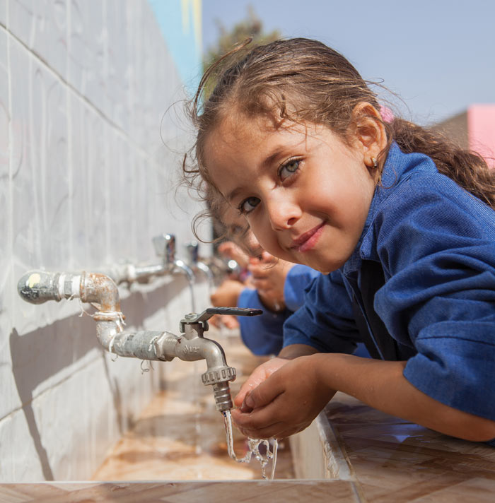 A student from the Bassa primary school, takes a drink of water from the school's tap. (MCC photo/Meghan Mast)