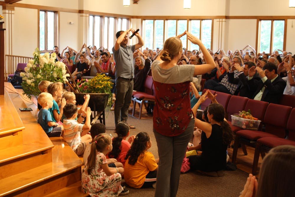 Crissman returned to the stage to lead the children's lesson, accompanied by fellow Kids Club worker, Melody Zimmerman. Energetic songs and storytelling soon had both children and adults involved in acting out Jesus' parable of sowing seed on different kinds of soil.
